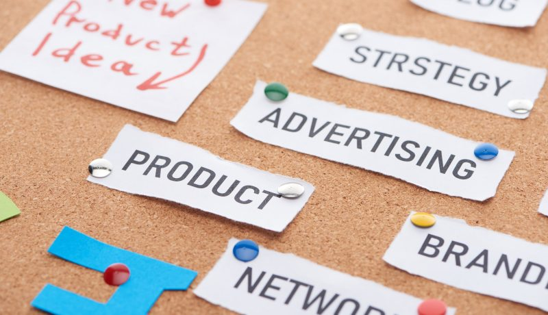 Paper Card With New Product Idea, Advertising, Blog,network Inscriptions Pinned on Cork Office Board